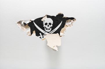 Hole in gypsum wall showing pirates flag. industrial espionage c
