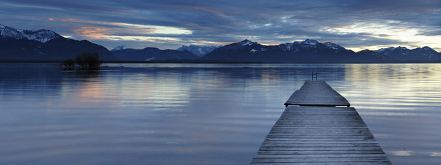 Wooden Pier into Lake Chiemsee at Sunset agains the Bavarian Alps, Bavaria, Germany