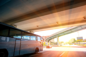 bus moves under bridge on highway