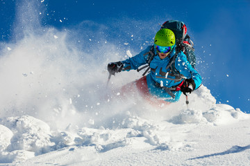 Freeride skier on piste running downhill