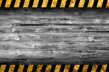 Grunge grey wood background with black and yellow warning stripes