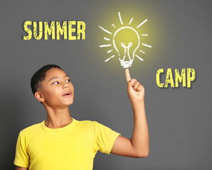 Cute afro american teenager and text summer camp on gray background. Summer holiday concept.