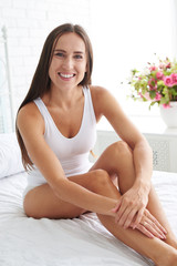 Happy smiling woman with her perfect tanned slender legs sitting