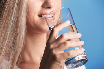 Beautiful girl drinking water on blue background