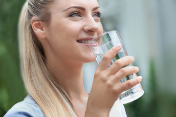 Beautiful girl drinking water on street