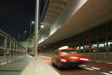 Motion blurred red taxi on Rainbow Bridge in Tokyo at night