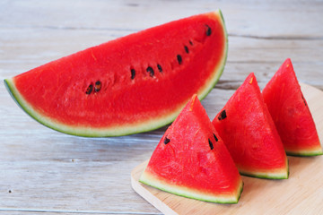 Close up of sliced watermelon on a wooden table.