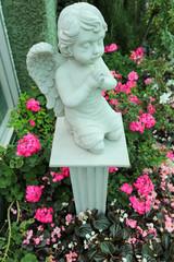 Statue child angle among pink flower.