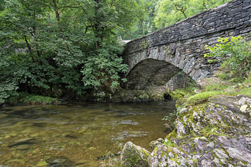 Great Langdale beck flows under Elterwater bridge. Elterwater is a popular meeting point for walkers and tourists exploring Great Langdale in the Lake District National Park, Cumbria, England.