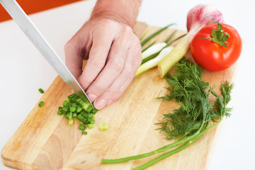 Closeup man's hand with a knife cut  green onion on a wooden board.