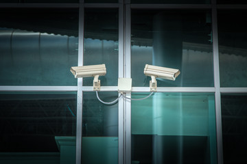 Two way CCTV  on glass office building background or dual security camera.