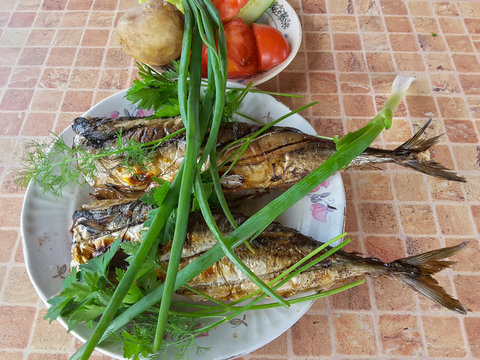 Fish grill on the plate, on table with greenary