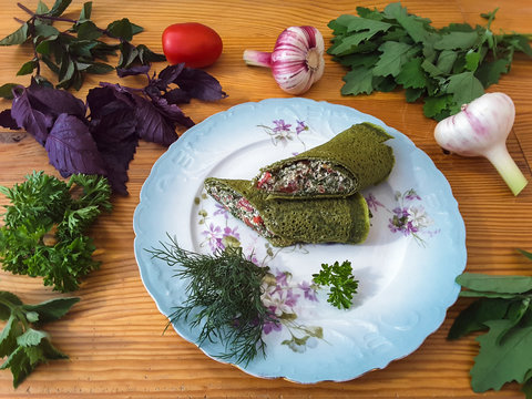 Green nettle roll with tomatoes and basil on plate, organic food with garlic and weed