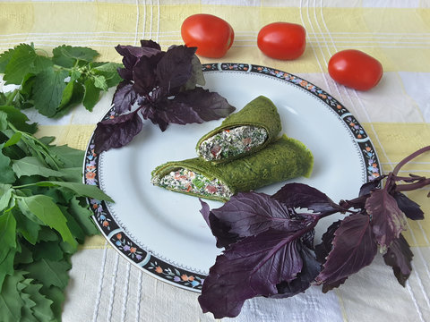 Green nettle roll with tomatoes and basil on plate, organic food with weed
