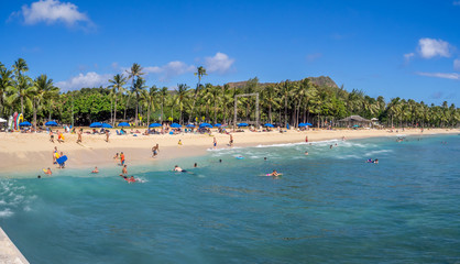 Sun lovers on Waikiki beach in Honolulu, Usa. Waikiki beach is neighborhood of Honolulu, best known for white sand and surfing.