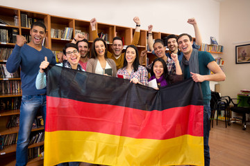 Students with hands raised and smiling faces present German coun