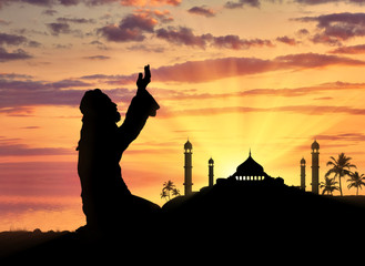 Muslim praying on a background of a mosque