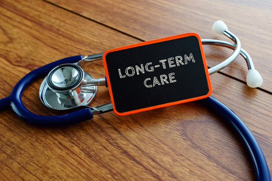 Medical concept.Word LONG-TERM CARE with stethoscope on wooden table.