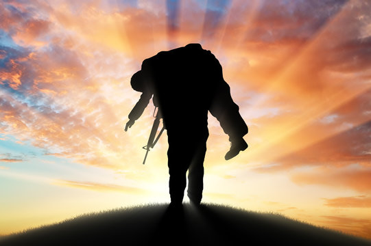 Soldier carries a wounded soldier at sunset