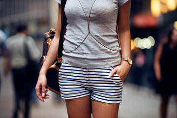 Outfit details of fashion elegant stylish woman posing. Female summer outfit with short striped blue and white shorts, grey t-shirt, modern leather backpack and jewelry watch standing on city street.