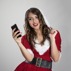 Beautiful Santa woman looking at mobile phone taking picture over gray studio background.