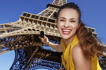 smiling young woman taking photo with camera in Paris, France