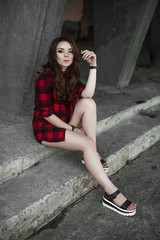 Beautiful young hipster girl posing and smiling near urban wall background in red plaid shirt, shorts, outdoors summer portrait.