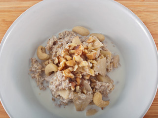 a bowl of oatflakes in soy milk with apple slices and nuts