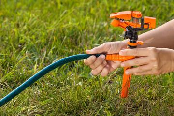 hands of gardener installing sprinkler for irrigation of lawn