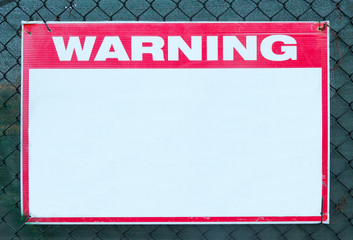 Warning Sign safety caution with blank white message at construction site grid boundary.