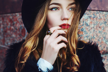 Outdoor portrait of a young beautiful fashionable lady wearing stylish black fur coat and wide-brimmed hat. Model looking aside. Female fashion concept. City lifestyle. Close up.