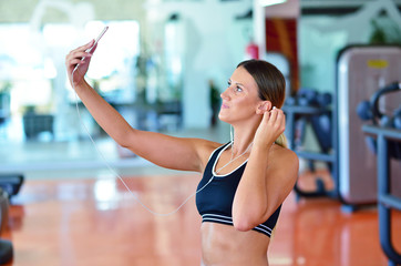 Beautiful young women taking a selfie during a break on a pole fitness class