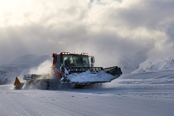 snowcat evening working on a slope