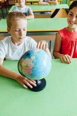 Child looks at a globe in a classroom