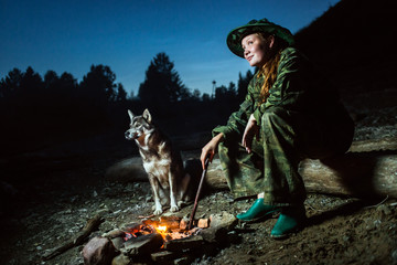 tourist girl with her dog around campfire at night