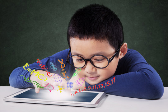 Boy learns with tablet on desk in class