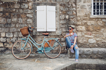 Young stylish girl drinking coffee while resting from her bike trip. Coffee break, then cycle.