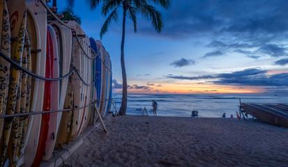 Surf board lines up on Waikiki beach at sunset