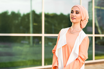 Young woman wearing hijab head scarf in city.