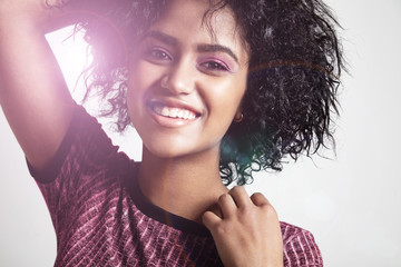 sunny portrait of smiling black woman with curly hair