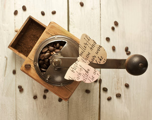 Paper butterfly on old coffee grinder, with coffee beans