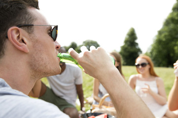 Young man drinking beer on picnic with friends
