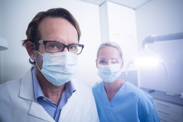Portrait of dental assistant and dentist wearing surgical mask