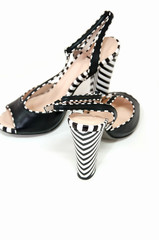 Pair of female high heeled slingbacks with striped heels isolated on white.