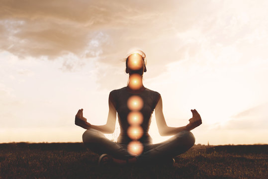 Woman practicing meditation in sunset, with chakras marked