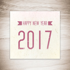 Happy new year 2017 on vintage paper over wood background