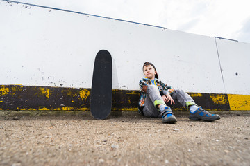 Boy sitting with skateboard on the rink and thinking about something