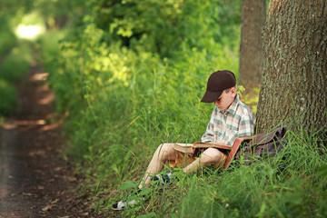 мальчик читает книгу в парке