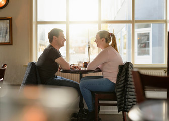 Young couple sitting in cafe, face to face, smiling