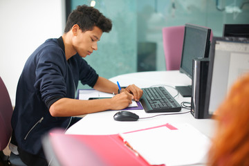 Young male college student at computer desk making notes
